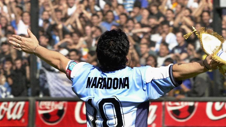 "In this file photo taken on November 09, 2001 Argentinian football star Diego Maradona greets the public in the ""La Bombonera"" stadium of Boca Juniors Athletic club in Buenos Aires. Argentinian football legend Diego Maradona passed away on November 25, 2020."